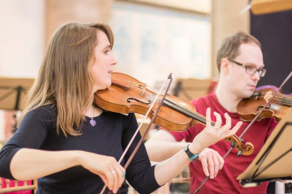 Amanda Babington leading a rehearsal with a male violinist